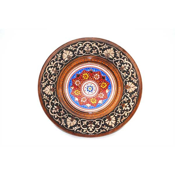 traditional wooden plate with red handcrafted design in the middle